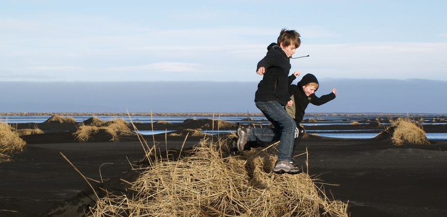 Kids playing on a black sand beach