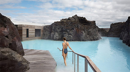 A woman enters the lagoon in the Retreat spa