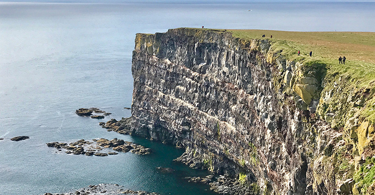 People walking on the edge of Látrabjarg sea-cliffs
