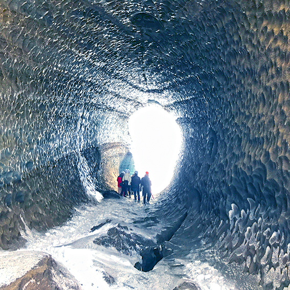 People walking through an Ice tunnel in Mýrdalsjökull glacier