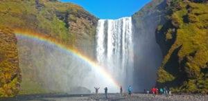 People enjoying a rainbow over Skógafoss waterfall
