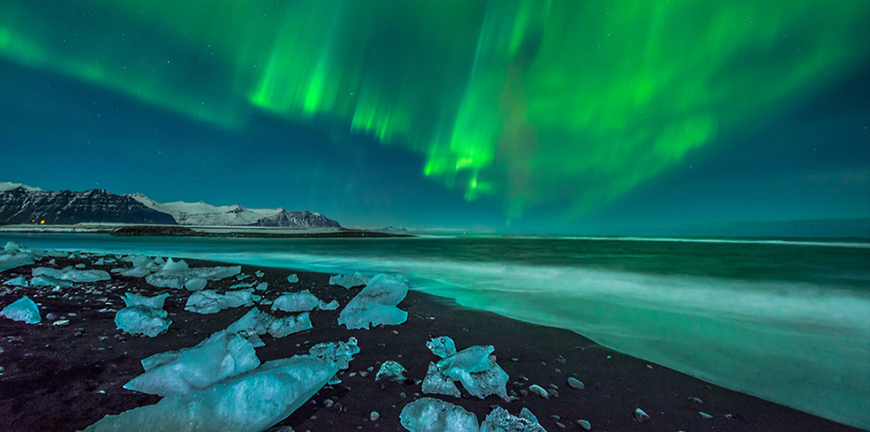Northern Lights and ice on a black sand beach