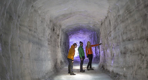 Three persons looking at an ice wall inside the Ice Tunnel