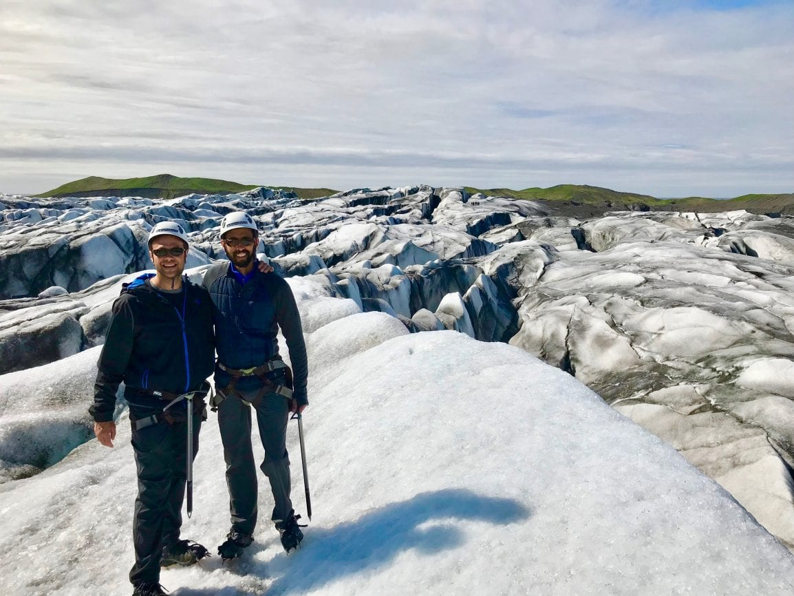 Two men standing on a glacial ice